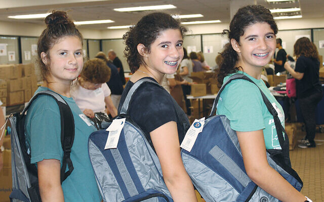 Federation volunteers show off backpacks in 2019.