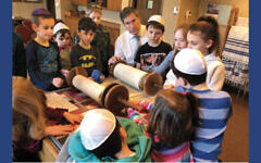 Rabbi Arthur Weiner of the Jewish Community Center of Paramus/Congregation Beth Tikvah shows a Torah scroll to a Hebrew school class.