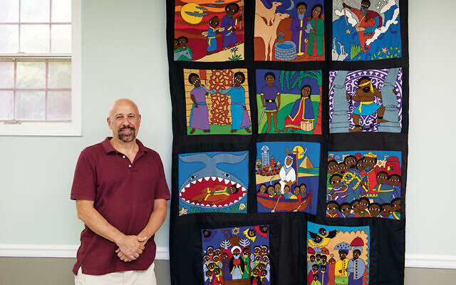 Rabbi Barry Schwartz stands by the mural his wife, Debbie, created from the Ethiopian Jewish folk art they have collected. (Courtesy Rabbi Barry Schwartz)