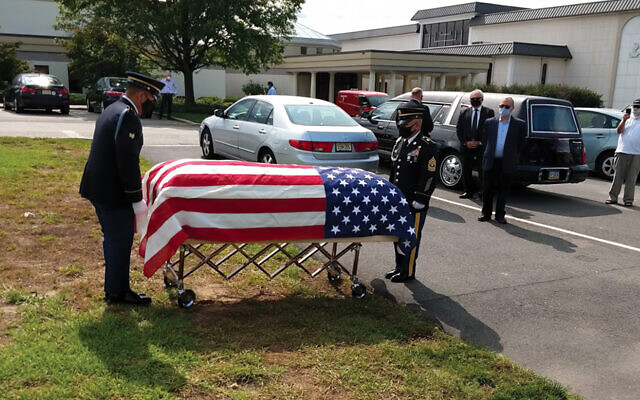 An honor guard prepares to ceremoniously remove the American flag from Philip Sieradski's casket. (Menachem Daum)