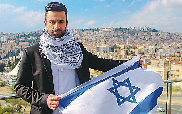 Yoseph Haddad stands with his country's flag; the backdrop is his hometown, Nazareth.