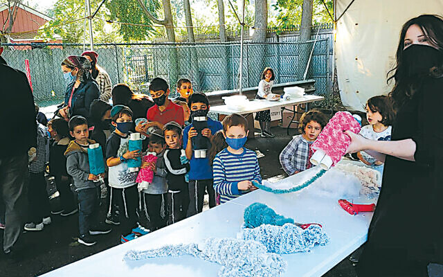 The children creating their Torahs with help from teacher Rivky Kumer, at right.