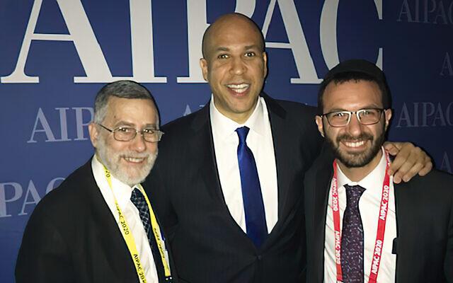 Senator Cory Booker stands between  Rabbi Menachem Genack and his son, Rabbi Yitzy Genack.