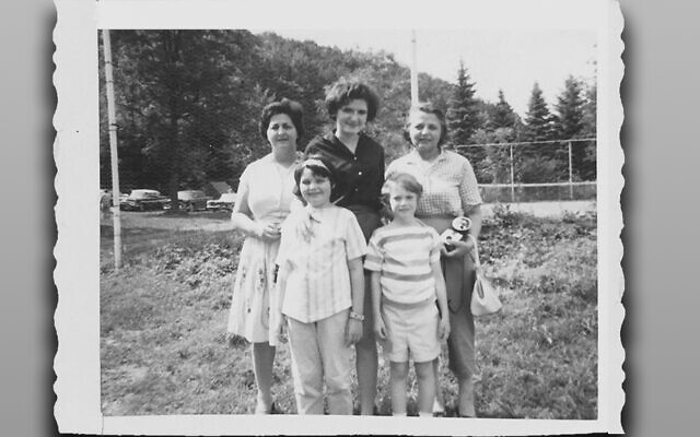 At summer camp on visiting day, Esther, the small blonde girl, and her cousin Jeanie are in front. Aunt Helen is behind Esther, and her sister Anita and a family friend also smile at the camera.