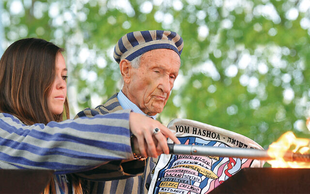 """Holocaust survivor Edward Mossberg of Morris Plains and his granddaughter, Jordana Karger, light a memorial torch in Auschwitz-Birkenau on Holocaust Remembrance Day on the 2016 March of the Living. This photo, by Yossi Zeliger, is the cover image of the book """"Witness: Passing the Torch of Holocaust Memory to New Generations,"""" compiled by Eli Rubenstein with March of the Living."""