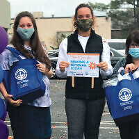 From left, co-chairs Penina Samuel, Tracy Limbardo, and Laurie Ann Weinstein celebrate reaching their goal — distributing nearly 3,000 gifts during a pandemic.