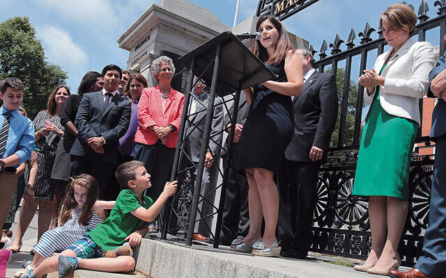 Mimi Lemay advocates for transgender rights in front of the Massachusetts State House in Boston as Jacob looks on.