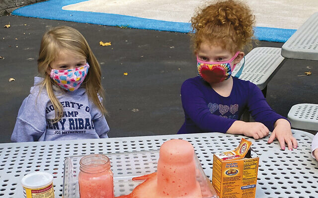 Early School students Evelyn Minde and Drew Delinko, observe a science experiment to see which would bubble over first, baking powder or baking soda. (Courtesy TBA)
