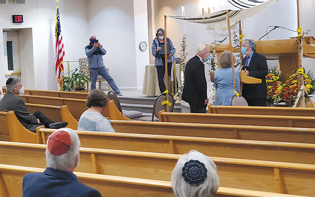 The socially distanced minyan watches as Miriam Edelstein and John Hecht get married.