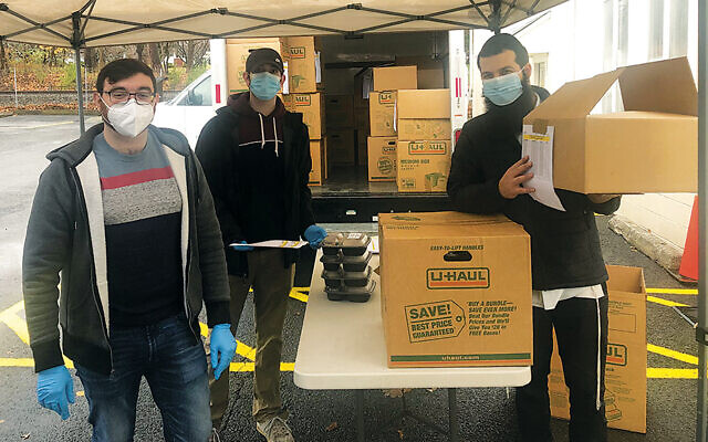 Brothers Matt and Michael Harvey, shown with Rabbi Mendy Lubin, helped distribute the dinners. (Courtesy Chabad)