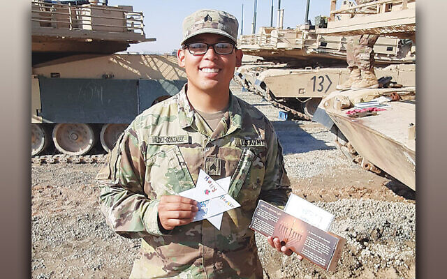 A soldier in Kuwait holds a card and gift and TBA Livingston students. (Courtesy TBA)