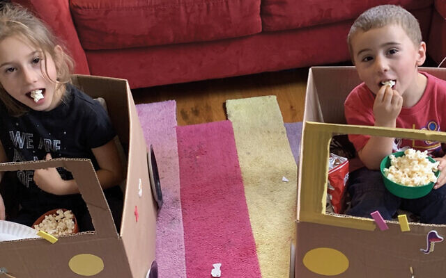 """Temple Sharey Tefilo-Israel's preschool sponsored a pandemic drive-in movie night; here, the synagogue's Cantor Rebecca Moses's children, Alexandra and Levi, munch popcorn in their """"cars."""" (TSTI)"""