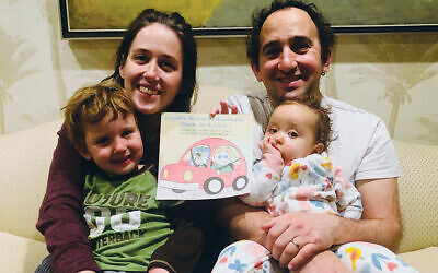 Kira and Andrew Wigod hold Cayleb, Charley, and the book they wrote.