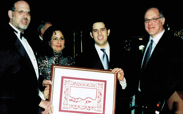 In 2004, David Shapiro, as Sinai's president, beaming at right, presented an award to Rabbi Mark and Linda Karasick as their oldest son, Zev, stood with them.