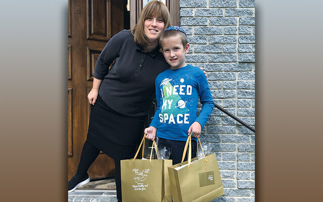 Here Zeesy Grossbaum and her son, Levi, prepare packages for pick up at an earlier event. (Courtesy FCBC)
