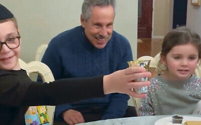 Andy Shechter of Mahwah with his grandchildren on the Zoom Havdalah program. (Courtesy Chabad)