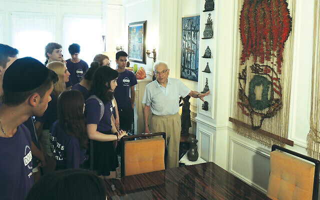 Ted Comet showS his late wife's tapestries to students from Congregation Rodeph Shalom in Manhattan.