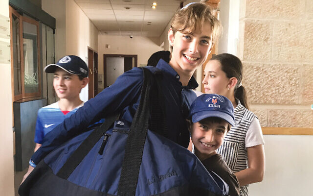 Caleb Rosenfeld holds a duffle bag full of hair on his way to Israel three years ago. (Photos Courtesy Caleb Rosenfeld)