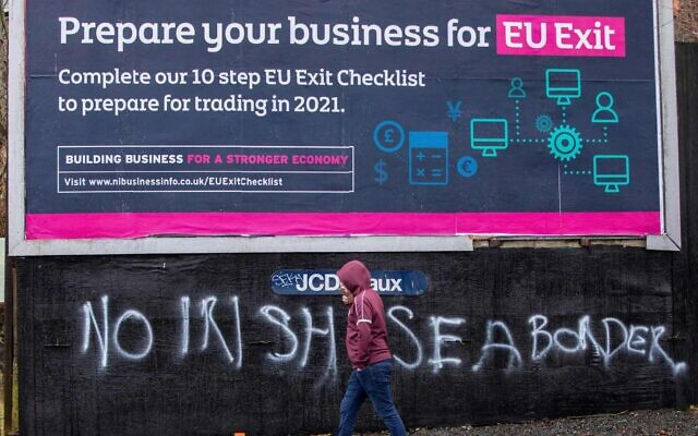 A man walks past a sign promoting Brexit and graffiti against an Irish sea border, in Belfast, Feb. 2, 2021. (Paul Faith/AFP via Getty Images)