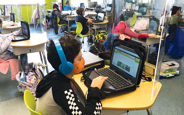 Masked, separated students study in a classroom at Gottesman RTW.