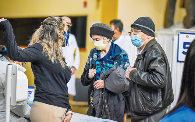 Above and below, staff at the JCC MetroWest welcomes Holocaust survivors as they arrive for their covid vaccines. (JCC MetroWest)