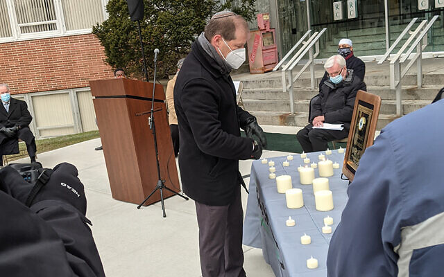Rabbi Craig Scheff lights a candle at the memorial.