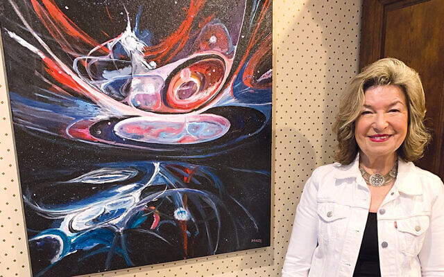 """Rosalind Dorlen stands next to one of her paintings, """"Birth."""""""