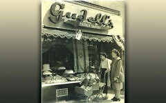 A young mother pushing a stroller, accompanied by an older woman — her mother, most likely — look in the window of Gudell's bakery. Note the Israeli flag in the window. (Courtesy Loretta Soloway)