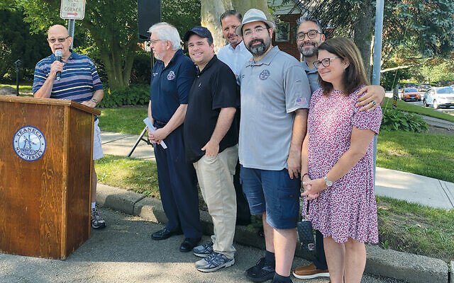 Paul Ostrow addresses the crowd. With him, from left, are Teaneck's Mayor Jim Dunleavy, Deputy Mayor Elie Y. Katz, town manager Dean Kazinci, and council members Keith Kaplan, Michael Pagan, and Karen Orgen.