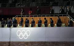 The emperor of Japan, International Olympic Committee president Thomas Bach, and others stand for a moment of silence during the opening ceremony of the Tokyo 2020 Olympic Games. (Martin Rickett/PA Images via Getty Images)