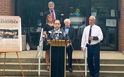 As Simon Wiesenthal Center's eastern director Michael Cohen speaks, Tenafly Council member Jeff Grossman stands at the top of the steps, Holocaust survivor Mark Schonwetter and his daughter, Ann Arnold, are behind Mr. Cohen, and Tenafly Mayor Mark Zinna is at the right.