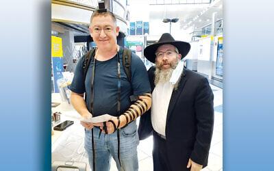 Rabbi Dovid Wilansky and a passenger at Newark Liberty Airport (Courtesy Bris Avrohom)