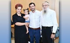 Chana Moria Dahan, holding baby Shuvi Shlomit, her husband, Netanel Dahan, and Ms. Dahan's father, Rabbi Yosef Mendelevich. (Eyal Cohen)