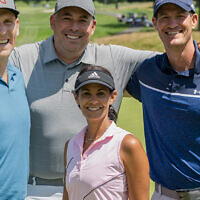 Dr. Robert Simon, Todd Forman, and and David Reichel stand behind Play Fore! The Kids Co-Chair Tracy Wolfson Reichel.