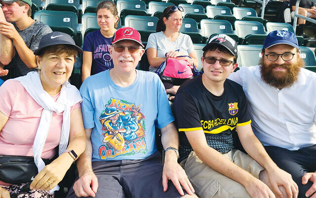 Rabbi Yosef Orenstein, right, with the Berzin family of Ramsey at the game. The Raikher family of Park Ridge are seated behind them. (Valley Chabad)