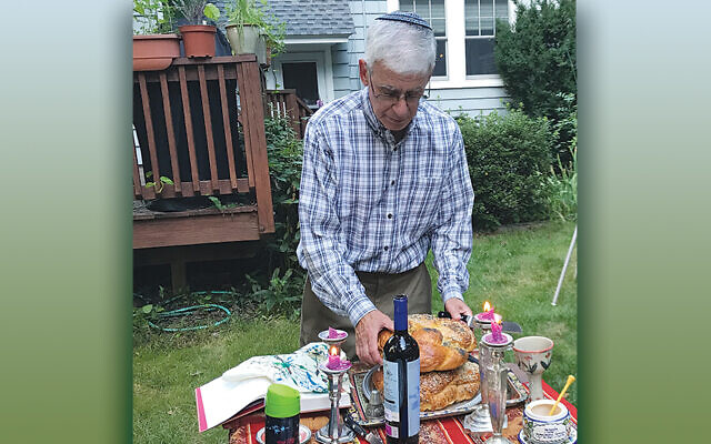 Andy Silver makes motzei in his backyard as his family watches.