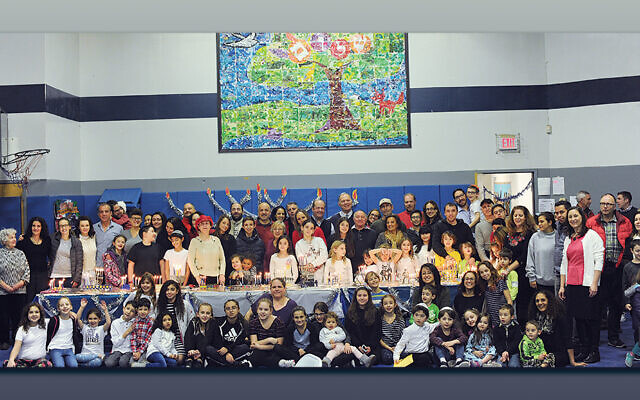 The school gathers for a community-wide menorah lighting in 2019.