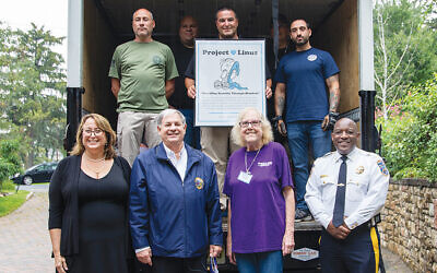 Bergen County Office of Emergency Management staff, in back row, are joined by Bergen County Commissioner Vice Chair Tracy Zur, Bergen County Executive Jim Tedesco, Project Linus member Leslie Maltz, and Sheriff Anthony Cureton in the front.