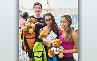 Joseph Feiler of Woodcliff Lake, Olivia Ferri of Allendale, and Ilana Schulman of Upper Saddle River with their packed backpacks for the kids. (Courtesy Chabad)