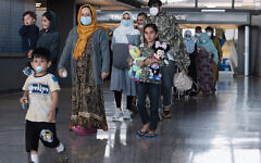 A family evacuated from Afghanistan is led through the arrival terminal at Dulles International Airport in the Washington area in August to board a bus that will take them to a refugee processing center. (Anna Moneymaker/Getty Images)