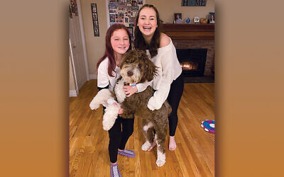 Sisters Isabella and Ellie Blumberg of Acton, Mass. and Winnie, their Bernedoodle
