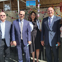 From left, Sinai's associate managing director Arielle Greenbaum Saposh, managing director Sam Fishman, dean Rabbi Dr. Yisrael Rothwachs, development director Pam Ennis, and communications director Abigail Hepner Gross stand with Holy Name's CEO Michael Maron, who is second from right. They're all at the hospital's annual Sukkot Lunch and Learn, in its sukkah, which flooding from Ida moved to the employee cafeteria patio. Mr. Maron drew on writing by Rabbi Jonathan Sacks to talk about coming together in crisis. Many members of Holy Name's staff — not all of them Jewish — come to the lunch, and they invite members of partner agencies to join them. (Jeff Rhode)