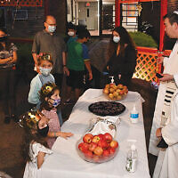Teaneck's Temple Emeth congregants and their children learned about Sukkot and enjoyed pizza in and goodies in the shul's sukkah with Rabbi Steven Sirbu and Cantor Ellen Tilem, standing at the right. (Barbara Balkin)