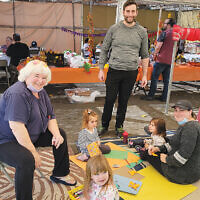 In Fair Lawn, Temple Beth Sholom's sukkah was decorated by its members and nursery school families. Here, Cantor David Krasner, his wife Sheri, their daughters, and Carol Zuchter and her granddaughter enjoy the afternoon.   (Courtesy Temple Beth Sholom)