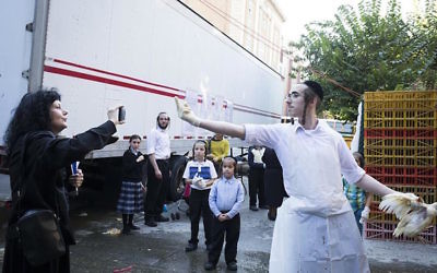 A Hasidic man expressing his views to an anti-kapparot activist in Brooklyn, New York, Sept. 17, 2015. JTA