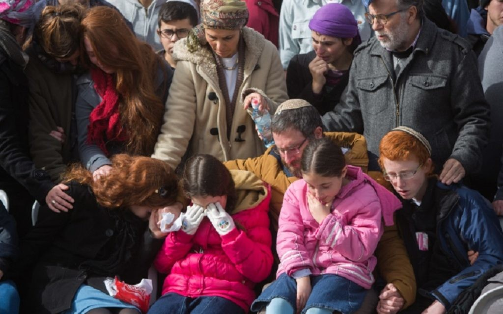Husband and children of Dafna Meir grieving at her funeral in Jerusalem the day after her stabbing death in the West Bank. JTA