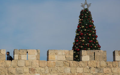 A Christmas tree standing behind the walls of the Old City of Jerusalem, Dec. 26, 2015. (Nati Shohat/Flash90)