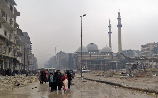 Syrian residents, fleeing violence in Aleppo's Bustan al-Qasr neighborhood, arrive in the Fardos neighbourhood after regime troops retook the area from rebel fighters, Dec. 13, 2016. (Stringer/AFP/Getty Images)