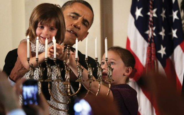 President Barack Obama holding up Kylie Schmitter, 4, to light a menorah as Kylie's sister, Lainey, looks on during a 2013 Chanukah reception at the White House. Getty Images