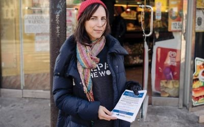 A volunteer with the Jewish social action group Repair the World gives out information on affordable healthcare in Crown Heights, Brooklyn, as part of the groups' MLK Day events.  COURTESY OF REPAIR THE WORLD